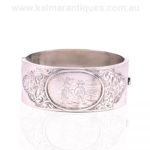 Antique silver bangle engraved with a young boy and girl on the front