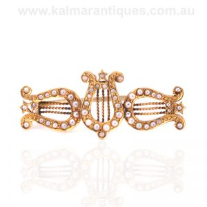 Antique lyre brooch set with natural seed pearls in 18 carat gold